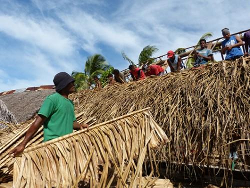 כל הגברים באי משתתפים בהחלפת הגג של בית הקהילה. צילום: טניה רמניק ואורן טל